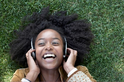 Woman with headphones lying on grass laughing